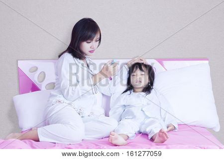 Portrait of young mother checking temperature her child while looking the thermometer
