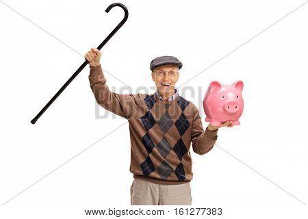 Overjoyed senior with a walking cane and a piggybank isolated on white background
