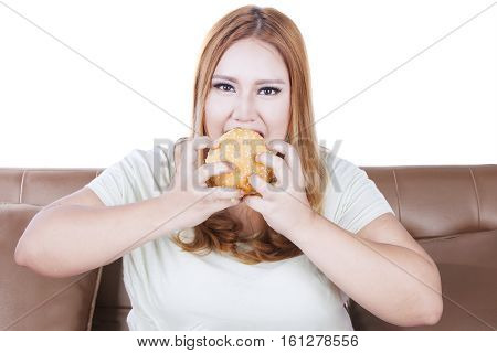 Portrait of a greedy blonde woman eating a big hamburger while sitting on the sofa concept of unhealthy lifestyle