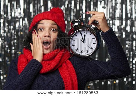 New Year eve concept. Surprised emotional woman in winter hat and scarf with hand on cheek holding with big alarm clock counting to midnight