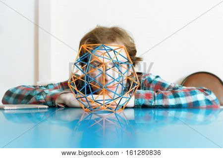 Coloured three-dimensional model of geometric solid against the background of the young man's face. Selective focus on foreground.