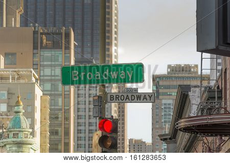 road sign of broadway in san francisco with a red light and buildings in the background