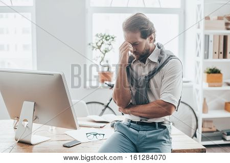 Stressed and tired. Young man in casual clothes massaging nose and keeping eyes closed while sitting on the desk in creative office