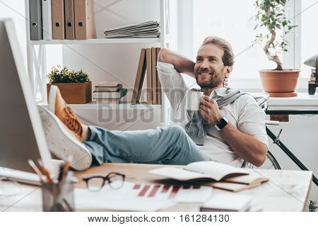 Dreaming about future. Handsome young man holding one hand behind head and holding a cup with another hand while sitting on working place in creative office
