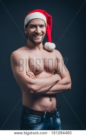 Sexy Santa. Young confident man keeping arms crossed and looking at camera while standing against black background
