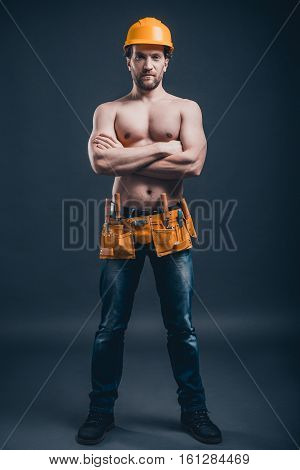 Construction worker. Full Length of young confident man keeping arms crossed and looking at camera while standing against black background