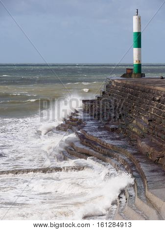 Choppy waves breaking by the lighthouse marks the entrance to the harbour and marina at Aberystwyth Ceredigion Wales.