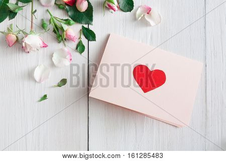 Valentine background with pink rose flowers and handmade paper card with hearts, top view on white rustic wood. Happy lovers day mockup, copy space