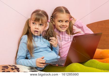 Two Girls Were Distracted From The Laptop And Looked Toward