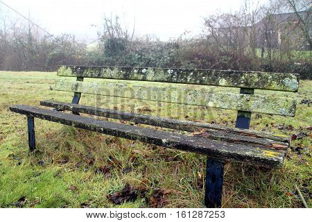 an old wooden bench abandoned an gnawed by the bod weather