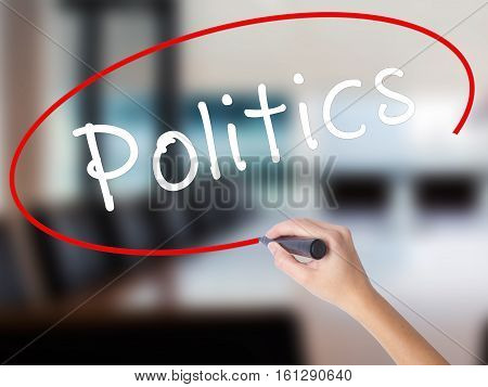 Woman Hand Writing Politics With A Marker Over Transparent Board
