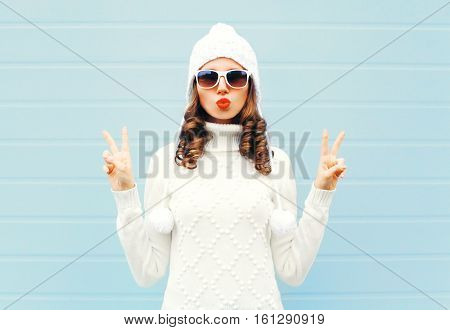 Fashion Woman Blowing Red Lips Makes Air Kiss Wearing A Heart Shape Sunglasses, Knitted Hat, Sweater