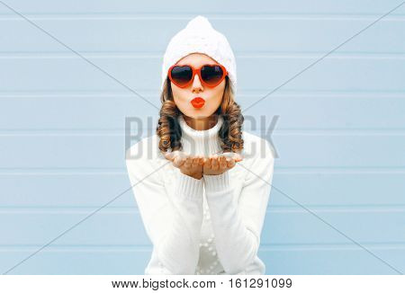 Happy Woman Blowing Red Lips Sends Air Kiss Wearing A Heart Shape Sunglasses, Knitted Hat, Sweater O