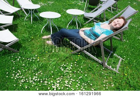 Girl Relaxing In Chaise Longue On A Summer Day