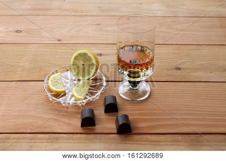 goblet of scotch whiskey Chocolate lemon on a wooden background with