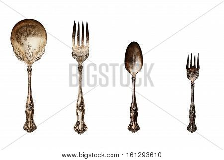 Vintage tarnished silverware isolated with clipping path over a white background. Image shot from overhead.