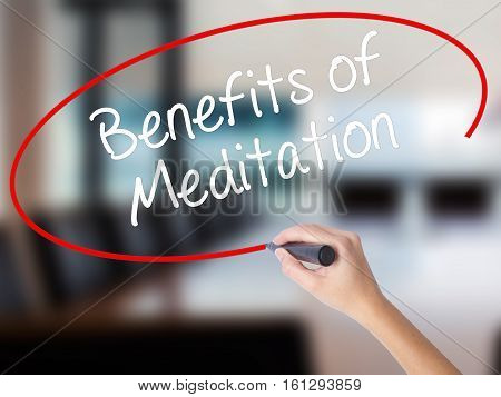 Woman Hand Writing Benefits Of Meditation With A Marker Over Transparent Board.