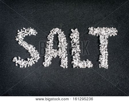 Salt word from coarse sea salt on stone. Flat lay or top view