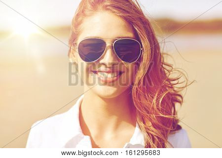 summer vacation, holidays, eyewear and people concept - smiling young woman in sunglasses on beach