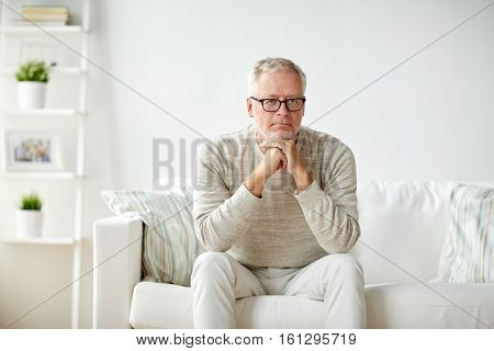 old age, problem and people concept - close up of senior man in glasses thinking at home