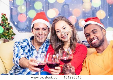 Multiracial friends celebrating Christmas holidays cheers vine glasses Santa Claus hat - Multiethnic family winter party at home with colorful blurred lights and snowfall background -