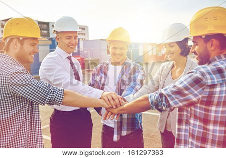 business, building, partnership, gesture and people concept - smiling builders and architects in hardhats with hands on top outdoors