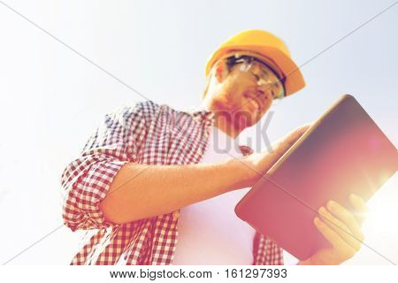business, building, industry, technology and people concept - close up of smiling builder in hardhat with tablet pc computer outdoors