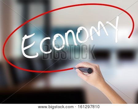 Woman Hand Writing Economy With A Marker Over Transparent Board.