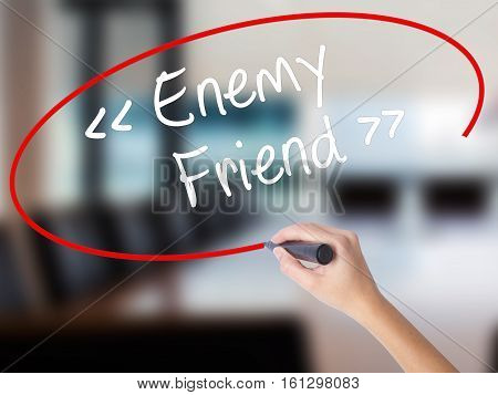 Woman Hand Writing Enemy - Friend With A Marker Over Transparent Board.