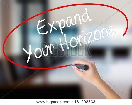 Woman Hand Writing  Expand Your Horizons  With A Marker Over Transparent Board