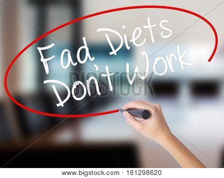 Woman Hand Writing Fad Diets Don't Work With A Marker Over Transparent Board
