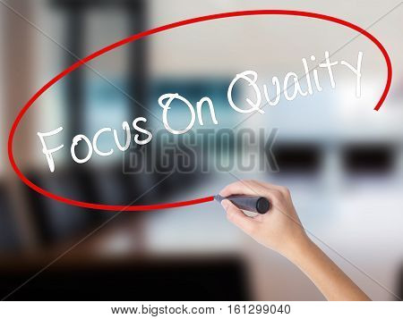 Woman Hand Writing Focus On Quality With A Marker Over Transparent Board