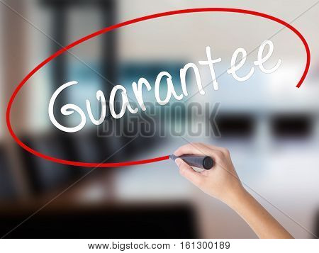Woman Hand Writing Guarantee With A Marker Over Transparent Board.