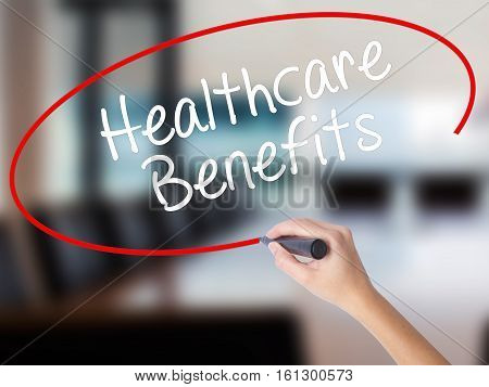 Woman Hand Writing Healthcare Benefits With A Marker Over Transparent Board