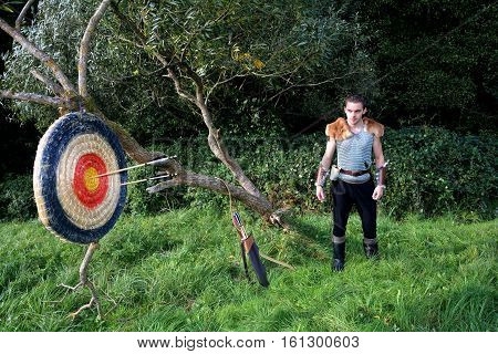 Medieval man stands in the Nature. Arrow, curve and quiver stands besides and target from straw with arrows hangs on the branch on left side