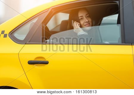 Girl talking on cell phone while sitting in yellow cab