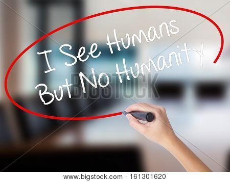 Woman Hand Writing I See Humans But No Humanity With A Marker Over Transparent Board.