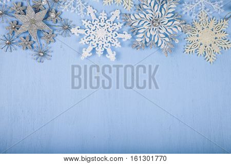 Silver Decorative Snowflakes On A Blue Wooden Background. Christmas Decorations Closeup.