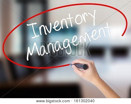 Woman Hand Writing Inventory Management With A Marker Over Transparent Board.