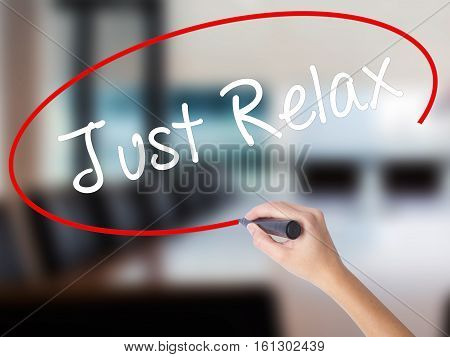 Woman Hand Writing Just Relax With A Marker Over Transparent Board