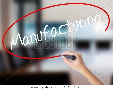 Woman Hand Writing Manufacturing  With A Marker Over Transparent Board.