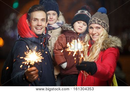 Happy family with bengal lights in park at night in new year
