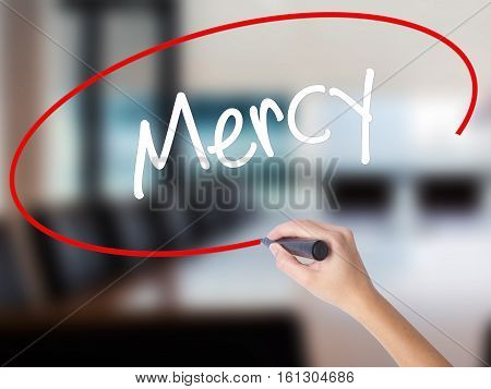 Woman Hand Writing Mercy With A Marker Over Transparent Board