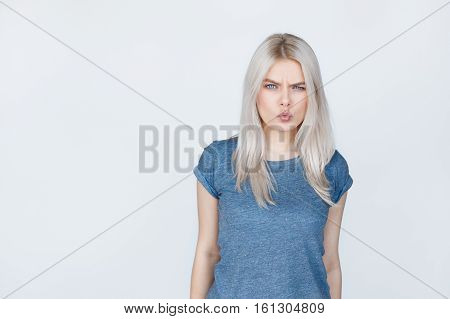 Angry Teenager girl over grey background. Blond young woman suspecting something with copy space