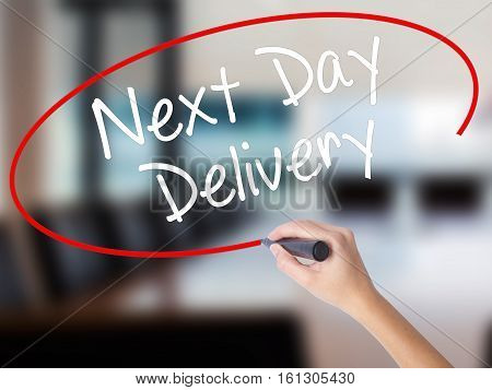 Woman Hand Writing Next Day Delivery With A Marker Over Transparent Board.