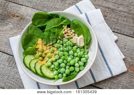 Ingredients for Green peas spinach basil pesto in a white bowl on a wooden background. Love for a healthy raw food concept.