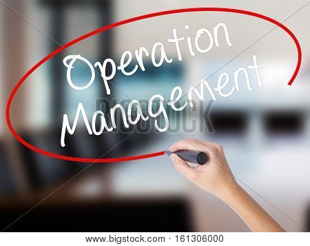 Woman Hand Writing Operation Management With A Marker Over Transparent Board.