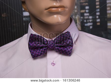 Pink shirt and bow tie placed on a mannequin