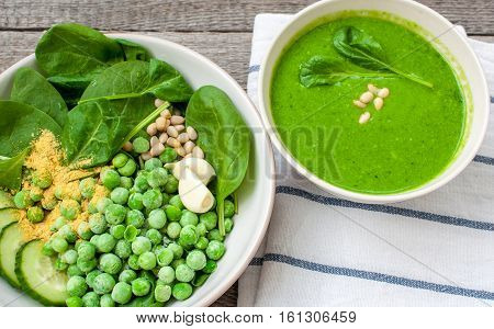 Green peas spinach basil pesto and Ingredients in a white bowl on a wooden background. Love for a healthy raw food concept.