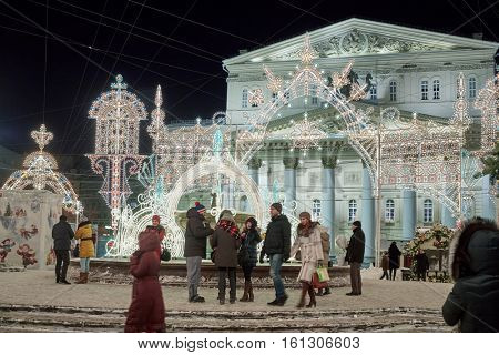 MOSCOW, RUSSIA - JAN 13, 2016: People walk next to the Bolshoi Theatre at Theatre Square decorated for new year holidays. Main theater of Russia begins its calendar since 1776.